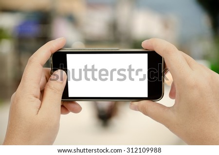 Smart phone in woman's hand on blur street background with clipping path