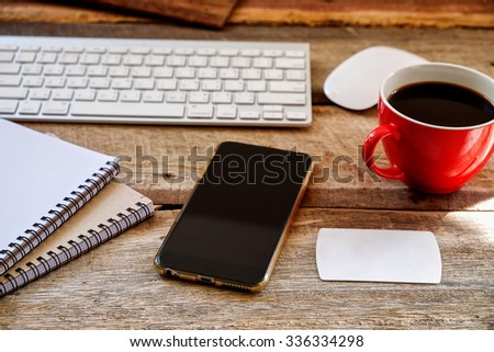 smart phone, keyboard notebook and, cup of coffee. on the wood table