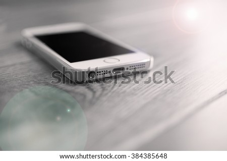 Smart phone lit by the morning sun from the window - stock photo