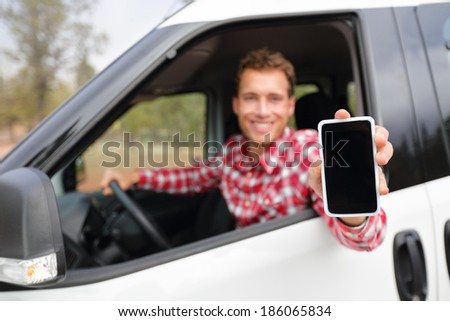 Smart phone man in car driving showing smartphone display smiling happy. Male driver using apps showing blank empty screen sitting in drivers seat. Focus on mobile cell phone. - stock photo
