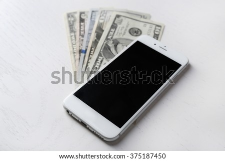 Smart phone on dollar banknotes over light table. Internet earning concept - stock photo