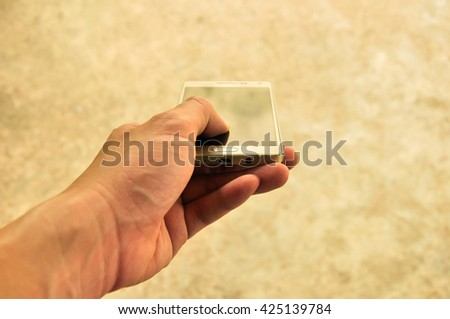 Smart phone on hand is a technology gadget for business and connected with worldwide by internet (With golden wall and orange light) - stock photo