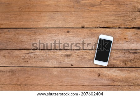 Smart phone on old wooden background - stock photo