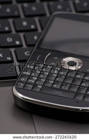 Smart phone on the laptop. Focus On Foreground. - stock photo