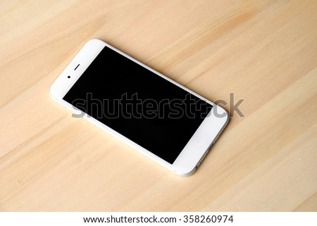 Smart phone on wooden table - stock photo