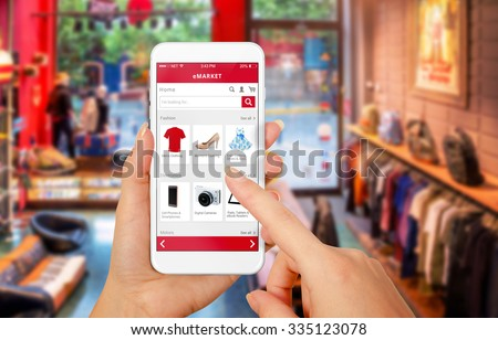 Smart phone online shopping in woman hand. Shopping center in background. Buy clothes shoes accessories with e commerce web site