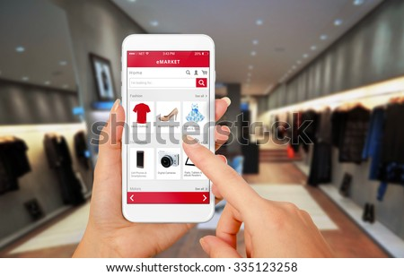 Smart phone online shopping in woman hand. Shopping center in background. Buy clothes shoes accessories with e commerce web site - stock photo