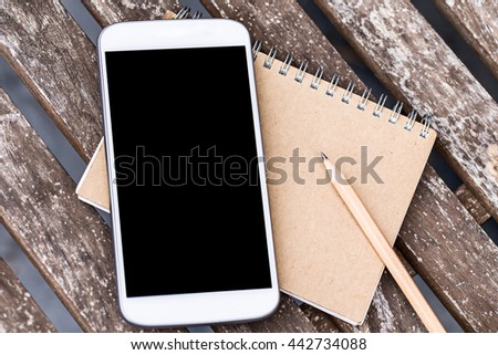 smart phone or cellphone with wooden pencil and recycle notebook paper over grunge wooden table background. - stock photo