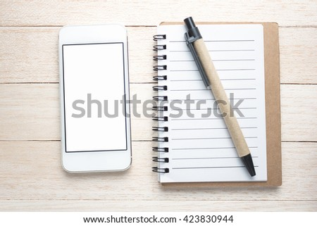 Smart phone, pen and notepad on wooden background close-up - stock photo