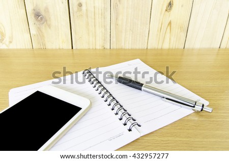 Smart phone, pen, leather stand and notebook on wooden background