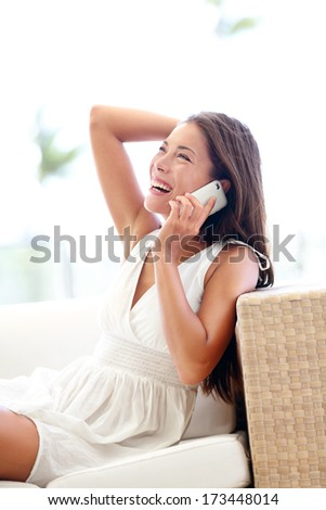 Smart phone pretty asian caucasian woman model talking cheerful sitting in white dress - hand on black hair - stock photo