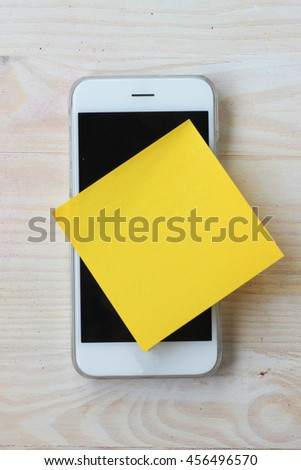 Smart phone reminder note. Yellow  paper sticky note glues on smart phone. - stock photo
