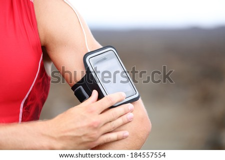 Smart phone running music closeup - male runner listening to music adjusting settings on armband for smartphone. Fit man fitness model working out outside in red sporty outfit. - stock photo