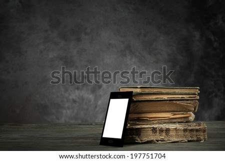 Smart-phone (self-designed) with blank display and old yellowed books - stock photo