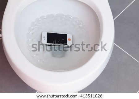 smart phone wet fell in the toilet bowl. - stock photo