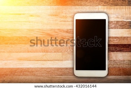 Smart phone with blank screen lying on wooden table, communication Smart phone, Smart phone Mockup - Sunlight filter effect - stock photo