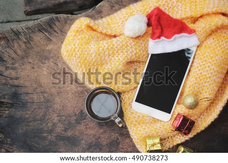 Smart phone with christmas hat and coffee cup