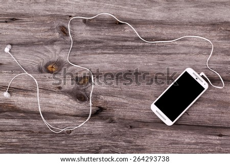 Smart phone with earphones against wooden background - stock photo