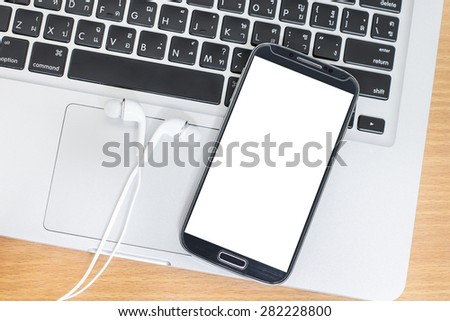 Smart phone with earphones and laptop on table - stock photo