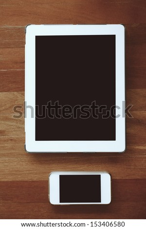 Smart phone with isolated screen on old wooden desk - stock photo