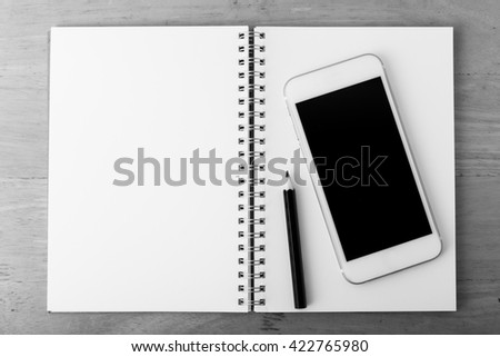 smart phone with note book on wooden table ,monochrome