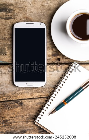Smart phone with notebook and cup of strong coffee on wooden background. Cellphone with writing set with espresso - stock photo