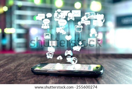 Smart phone with social media related icons glowing over screen and soft focus. - stock photo