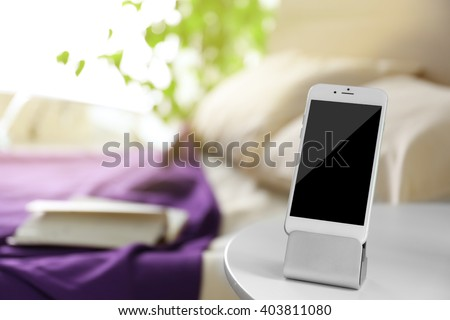 Smart phone with stand on a bedside table in a room - stock photo