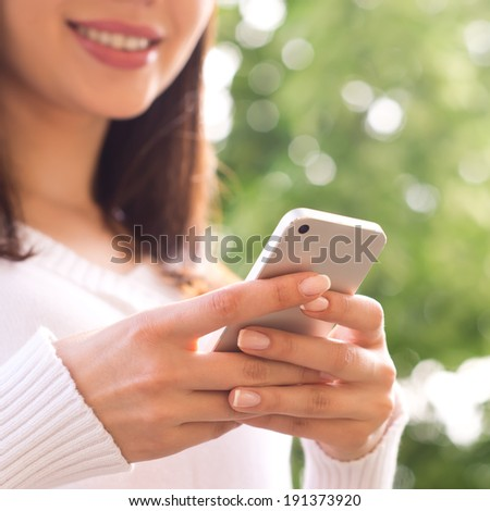 Smart phone. Young woman texting on her mobile phone - stock photo