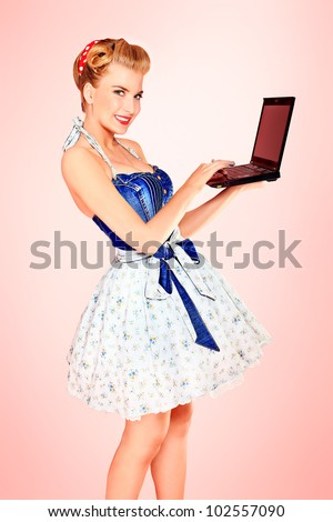 Smart pin-up girl posing over pink background with a laptop. - stock photo