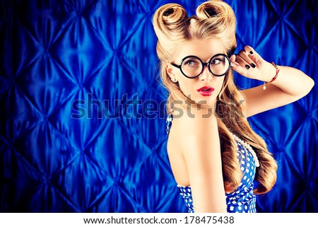 Smart pin-up woman with retro hairstyle and make-up wearing big round glasses. - stock photo