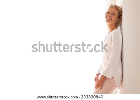 Smart professional business woman smiling and leaning on a wall by a glass door with sunny light, relaxing and enjoying her aspirational lifestyle, indoors. Home interior with businesswoman standing. - stock photo