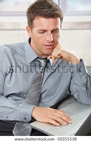 Smart professional businessman looking down on laptop computer with small smile hand on keyboard.