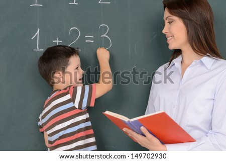 Smart pupil. Cheerful little boy writing on the blackboard and looking at his teacher standing near him - stock photo