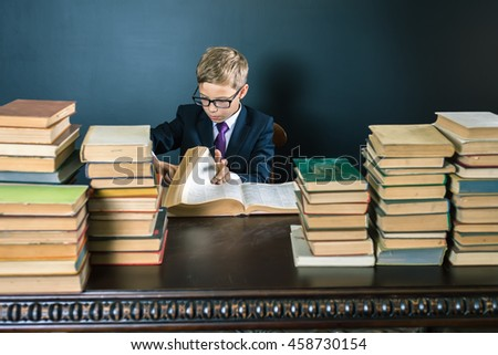 Smart school boy reading a book at library. Table with many books and one green apple. Child dressed in school uniform and glasses. Blackboard. Student. Concept of education. Scientist kid