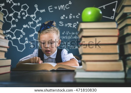 Smart school girl reading a book at library. Physics and chemistry formulas at blackboard. Table with many books and one green apple. Student. Concept of education