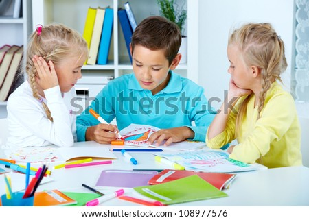 Smart schoolboy and twin girls drawing with colorful highlighters