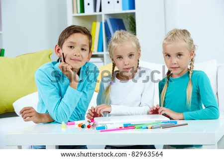 Smart schoolboy and twin girls looking at camera