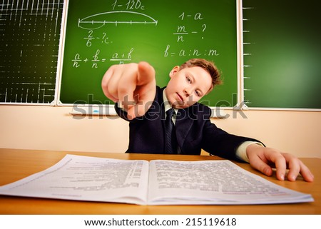 Smart schoolboy at a classroom points his finger at the camera. Education. - stock photo