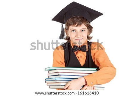 Smart schoolboy in academic hat holding a stack of books. Isolated over white. - stock photo