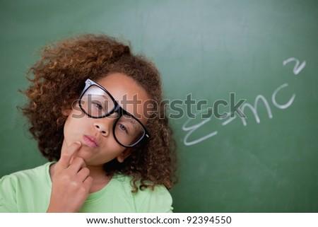 Smart schoolgirl thinking in front of a blackboard - stock photo