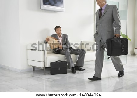 Smart senior businessman walking past a man with newspaper in office hallway - stock photo