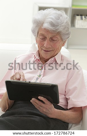 Smart Senior woman using a laptop at home sitting on the sofa in the living room reading information on the screen with a smile