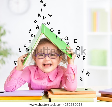Smart smiling kid in glasses taking refuge under book roof from falling letters - stock photo