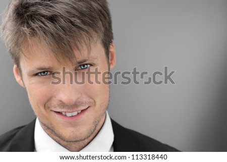 Smart smiling young businessman against gray background - stock photo