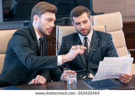 Smart solutions for business. Two good-looking managers in black suits looking at the business data and discussing business trends - stock photo