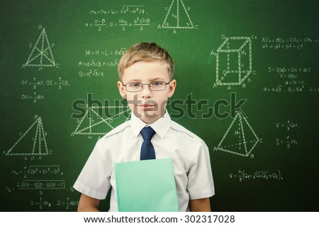 Smart student or schoolboy with a notebook, dressed in school uniform and sunglasses standing near blackboard scribbled with chalk - formulas and drawing. Concept of intelligent and scientist boy - stock photo