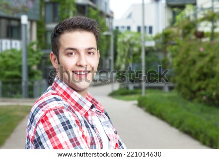 Smart student with checked shirt laughing at camera - stock photo