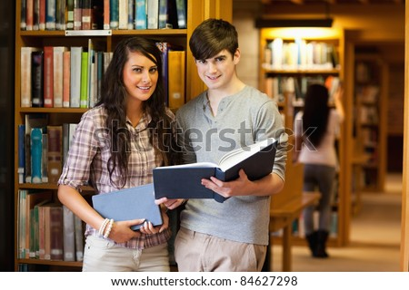 Smart students with a book in a library - stock photo