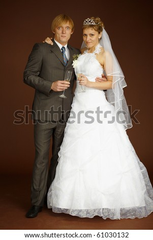 Smart studio portrait of the groom and the bride with wine glasses - stock photo